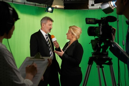 Female talent presenter Interviewing In St Louis Video Television Studio With Crew In Foreground